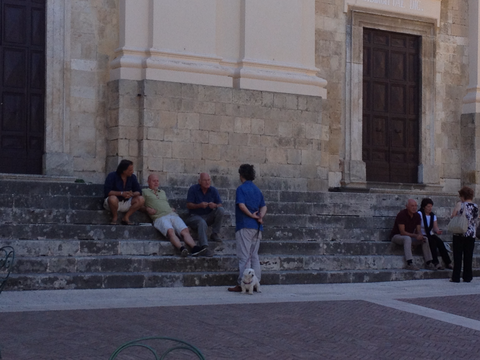 Men chatting on the stair to a church in Calvi dell'Umbria, Italy