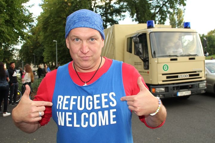 "A man with ""refugees welcome"" written on his shirt"