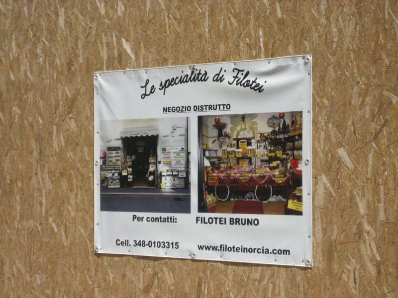 """Photos of the destroyed shop behind the """"curtain"""" and indication of where to contact the owner"""