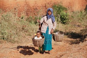 Woman carrying water and child